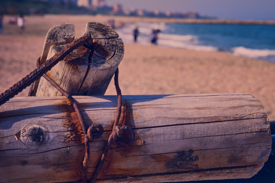 傍晚大海沙滩生锈铁丝捆木头