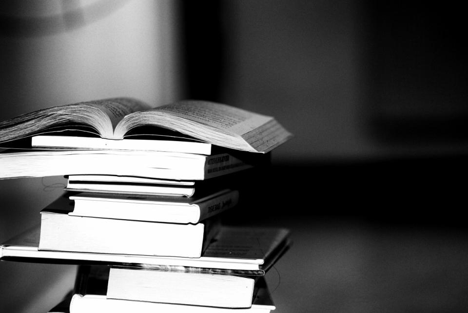 黑白色调打开的书本放在一堆书本上