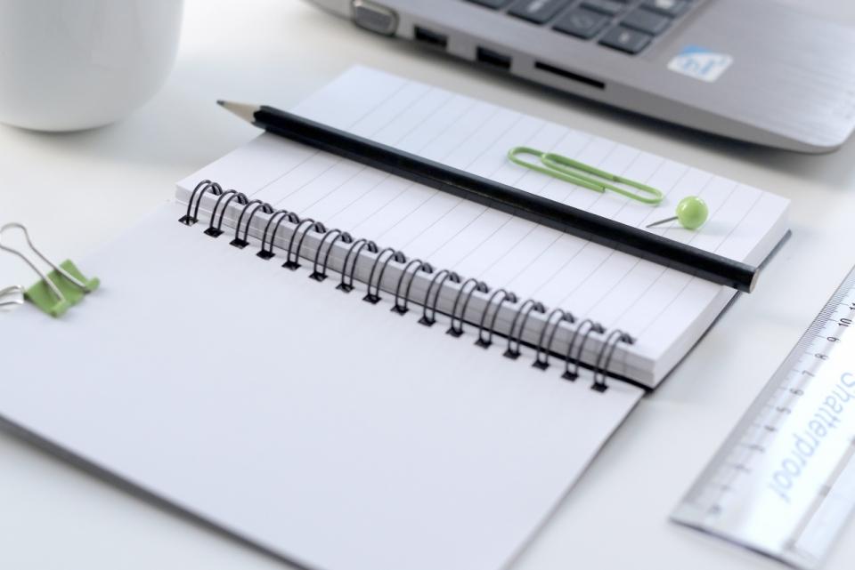 办公桌上摆放的笔记本铅笔杯子与尺子图片