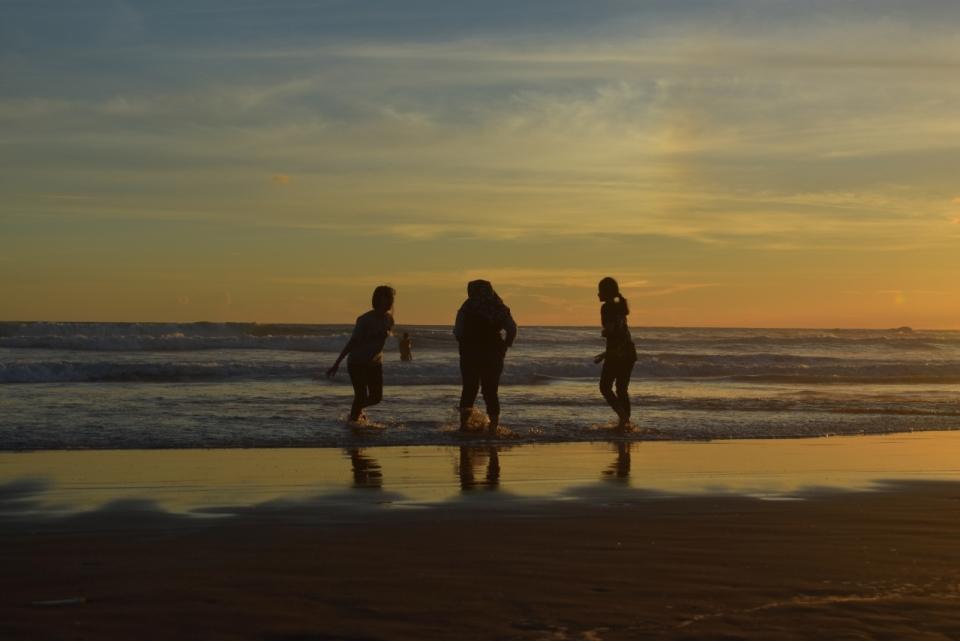 傍晚天空自然大海沙滩上女性们