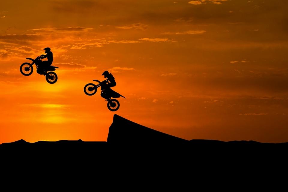 夕阳晚霞下骑摩托车飞跃土坡的两名车手