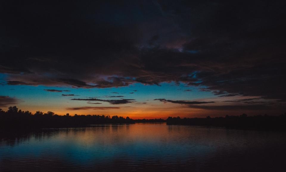 傍晚湖泊乌云压顶自然风光晚霞蓝天镜面
